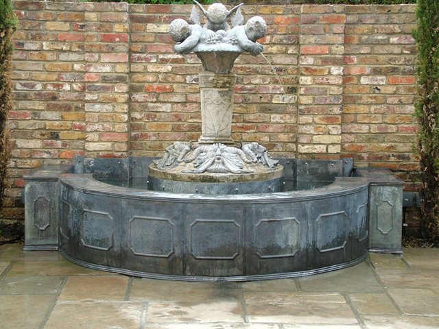 Lead wall frensham panel fountain with spouting cherubs in claph